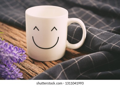 Happy cup with black tablecloth and beautiful flower on the wooden table. Concept about happiness and waiting for someone.Vintage Style with copy space