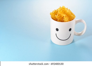 Happy cup with fusilli pasta on blue background. Love and relationship concept with copy space. Homemade Cooking. Food Preparation. Creative Style for designed work. Happiness in the kitchen.