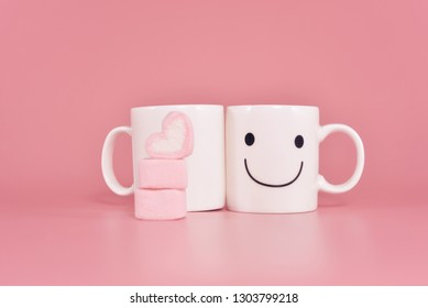 Happy cup with marshmallows in the shape of heart on pink pastel background.Concept about love and relationship.Creative colorful greeting card. Lovely couple with happiness.Valentine Day
