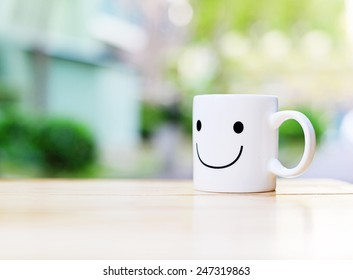 Happy cup on wood table. Concept about happiness and waiting for someone.