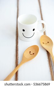 Happy cup with smiley spoons on the white wooden table. Concept about happiness and waiting for someone. (Selective Focus for designed-work)