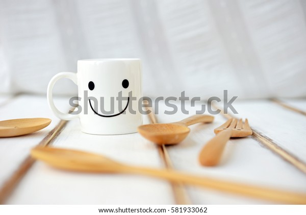 Happy cup with wooden spoons on the white wooden table. Concept about happiness and waiting for someone. (Selective Focus for designed-work)