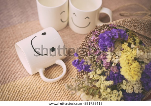 Happy cups with dries flowers on the bed. Concept about love and relationship