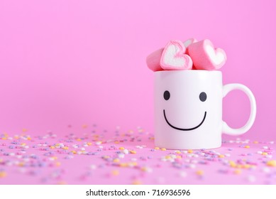 Happy cups with marshmallows in the shape of heart on pink pastel background. Concept about love and relationship. Love Yourself.  Happiness idea for design work with copy space. Valentine's Wallpaper
