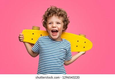 Happy curly boy laughing and holding bright colored skateboard over vibrant pink background isolated