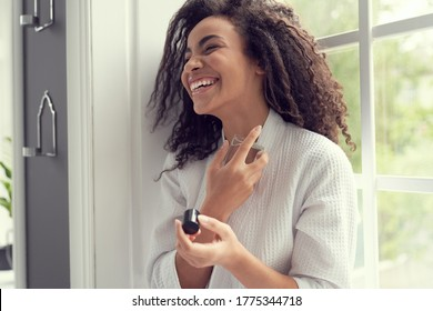 Happy curly female is having fun while holding bottle of perfume and spraying it on neck indoors