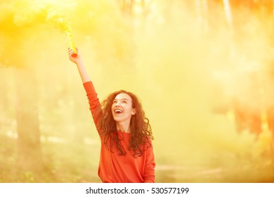 Happy curly girl with colorful smoke bomb in her hand running Outside. Yellow background. Hipster young woman