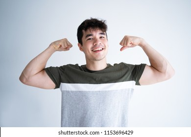 Happy curly guy keeping fit and healthy lifestyle. Cheerful young mixed race man flexing biceps. Strength and self pride concept