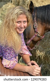 Happy Curly haired blonde girl and her horse near haystack