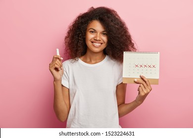 Happy curly haired lady holds menstruation calendar with marked pms days and tampon, dressed in casual white t shirt, isolated over pink background, advertises protective absorbent for menses