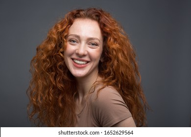 Happy curly red-haired woman with beautiful smile, holding her hair with her hands. On an isolated gray background. Concept: happiness and emotions