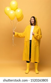 happy curly woman in yellow raincoat and wellies holding balloons on yellow background