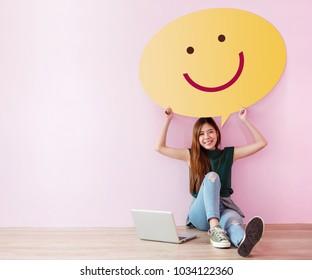Gutes Kundenkonzept. Review und Feedback ihrer Erfahrung für Zufriedenheit Survey Online. Junge Weibliche in fröhlicher Haltung, erheben Sie die Sprechblase mit Smiley Face. Setzen Sie sich auf den Boden mit Laptop