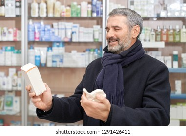 Happy customer of drugstore choosing medicaments for health care. Mature man holding in hands medicines and prescription paper. Bearded man wearing in coat and scarf smiling.