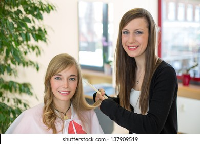 Happy customer getting her hair cut by hairdresser or stylist in salon