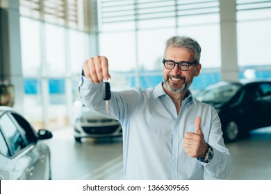 happy customer holding car keys and showing thumb up in car showroom