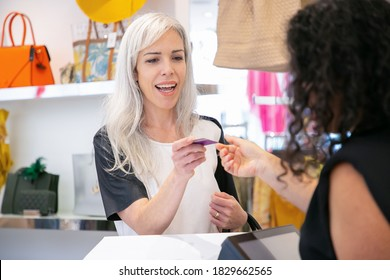 Happy customer paying for purchase in fashion store. Woman giving credit card to cashier in clothes shop. Medium shot. Shopping concept