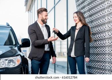 Happy customer receiving keys from a new car standing near the modern avtosalon