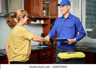 Happy customer shaking hands with repairman and signing invoice on clipboard standing in the kitchen at home