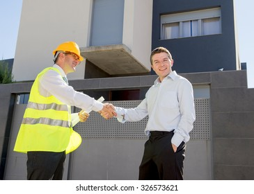 happy customer smiling and constructor foreman worker with helmet and vest holding blueprints handshake agreement in real state business and housing industry concept