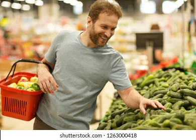 Happy customer standing and choosing green fresh cucumbers in section with vegetables in supermarket. Cheerful man smiling and holding red basket with products in hands.