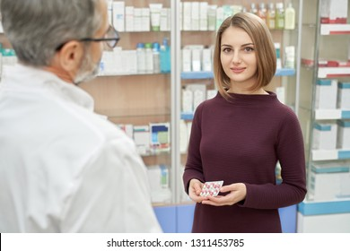Happy customer standing near pharmacist, holding blister pack with pills. Beautiful woman looking at camera, posing and smiling. Bearded, mature man in white coat helping clients in pharmacy.