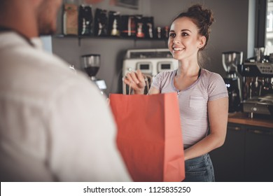 Happy customer taking paper bag after shopping at coffee shop