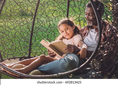 happy cute african american girl reading book while sitting in swinging hanging chair with granddad