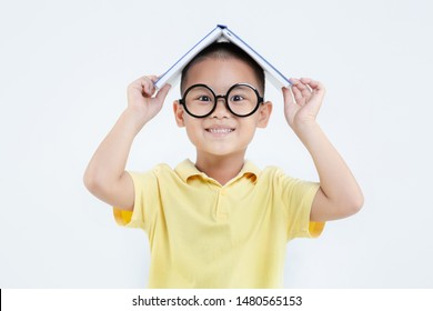 Happy cute Asian boy holding book over head thinking on white background isolated