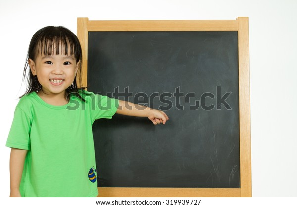 Happy cute Asian Chinese toddler girl standing beside a blank blackboard at home, preschool, daycare or kindergarten in plain white isolated background.