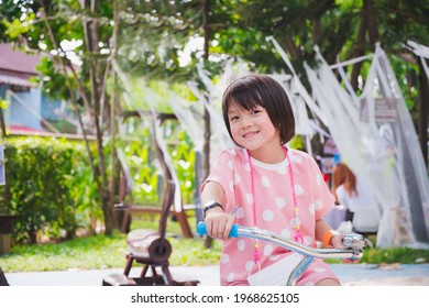 Happy cute Asian girl riding her bicycle at the playground. Fun kid wearing white polka-dotted pink shirts. Little child smiled sweetly. Children with short hair, black age 5-6 years old.
