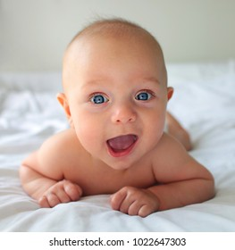 Happy cute baby boy on bed at home