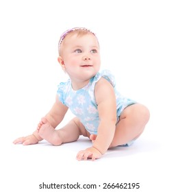 Happy cute baby girl sitting on the floor isolated on white background, cheerful funny child in the studio, innocence and purity concept