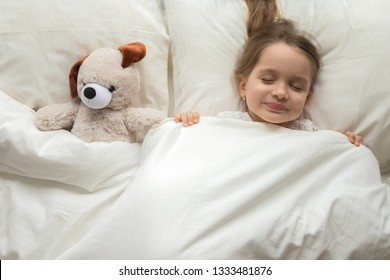 Happy cute baby girl sleeping with teddy bear toy in comfortable bed lay on pillow covered with warm blanket duvet, little kid fall asleep in bedroom, good night healthy child sleep concept, top view