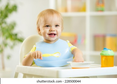 happy cute baby kid boy eating food itself with spoon
