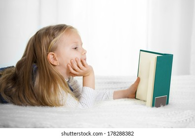 happy cute blonde haired school girl wearing a school uniform reading a book lying on the bed