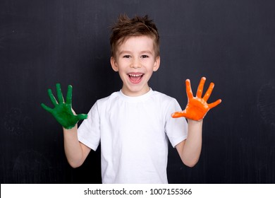 Happy cute boy colors his hands. Doing Finger painting. Art therapy for children. Psychology of the child's personality. Help gaining confidence. Drawing. Creativity and education concept.