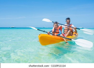 Happy cute boy and his father kayaking at tropical sea on yellow kayak
