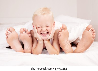 happy cute boy with his mother and father under the blanket in bed at home