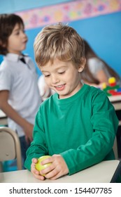 Happy cute boy holding smith apple with classmate in background at kindergarten