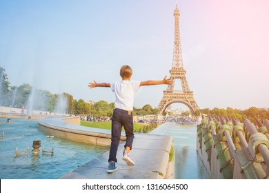 Happy cute boy running in centre of Paris. Background of Eiffel tower. Travel concept