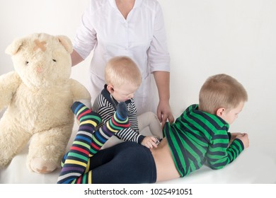 Happy cute boys playing with stethoscope at doctors office, hugging teddy bear bear and smiling at camera. The concept of family health. Female pediatrics. Copy space