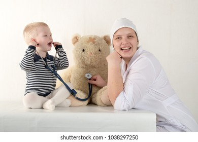 Happy cute boys playing with stethoscope in doctors office, hugging plush toy bear and smiling at camera. Female pediatrics. Copy space