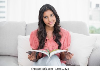 Happy cute brunette sitting on couch holding magazine in bright living room
