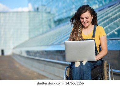 happy cute businesswoman in wheelchair working using a laptop, disability overcoming concept. blurred background, studio shot.copy space.job, profession, occupation