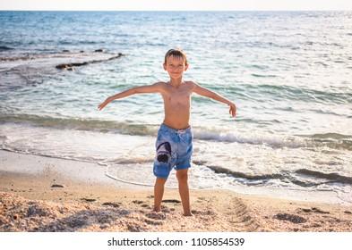 Happy cute child enjoying summer family vacation at sea beach