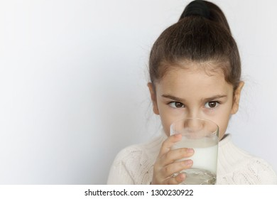 Happy cute child girl drinking yogurt on white background. Whiskers from yogurt.
