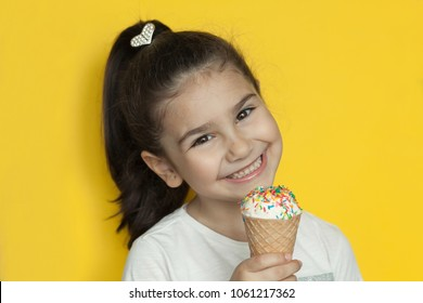 Happy and cute child girl eating ice cream
