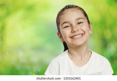 Happy cute child girl on the blur green background