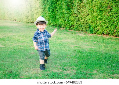 Happy cute child having fun in the garden.Smiling and running on green grass.